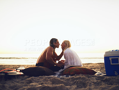 Buy stock photo Shot of a young affectionate couple sharing a tender moment during a date on the beach at sunset