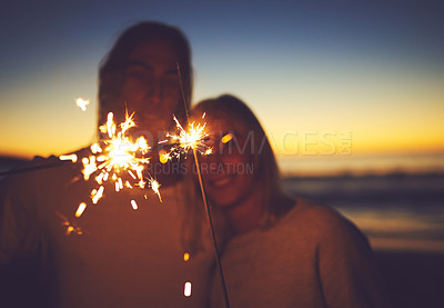 Buy stock photo Shot of a young couple playing with sparklers on the beach at night