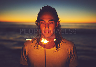 Buy stock photo Shot of a young man holding a sparkler at the beach at night
