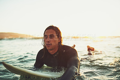 Buy stock photo Shot of a young man paddling on a surfboard in the sea