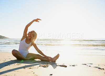 Buy stock photo Full length shot of an attractive young woman doing a yoga stretch early in the morning on the beach