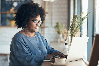 Buy stock photo Shot of an attractive young businesswoman sitting and working on her laptop in a coffee shop during the day