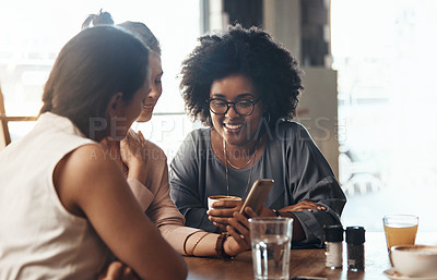 Buy stock photo Shot of attractive young women sitting together and smiling while looking at a cellphone in a coffee shop