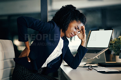 Buy stock photo Shot of a young businesswoman suffering with back pain and a headache while working in an office at night