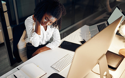 Buy stock photo High angle shot of a young businesswoman suffering with neck pain while working in an office at night
