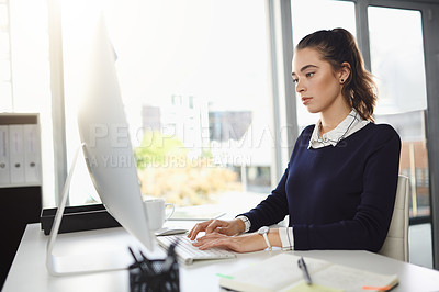 Buy stock photo Shot of an attractive young businesswoman sitting at her desk and using her computer in a modern office