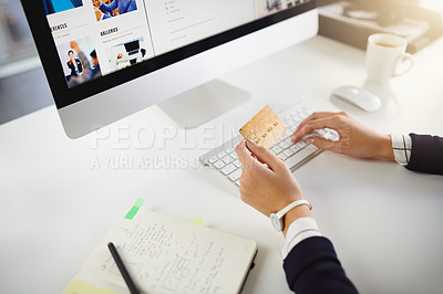 Buy stock photo Shot of an unrecognizable young businesswoman holding a bank card and using her computer in a modern office