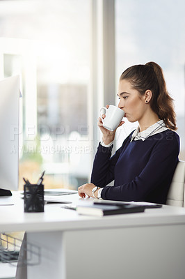 Buy stock photo Shot of an attractive young businesswoman sitting at her desk and enjoying a cup of coffee in a modern office
