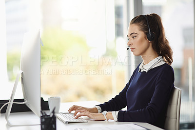 Buy stock photo Shot of an attractive young businesswoman wearing a headset and using her computer at her desk in a modern office
