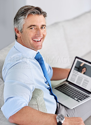 Buy stock photo Portrait of a mature businessman smiling and sitting on a sofa while working on his laptop indoors