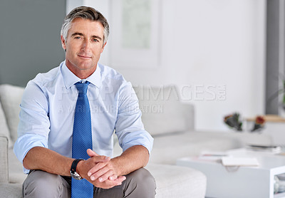 Buy stock photo Portrait of a confident mature businessman sitting on a sofa indoors with his hands clasped