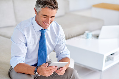 Buy stock photo Shot of a confident mature businessman sitting on a sofa indoors while working on a tablet