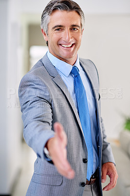 Buy stock photo Portrait of a mature businessman wearing a suit and standing indoors while extending his arm for a hand shake
