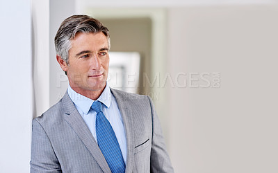 Buy stock photo Shot of a confident mature businessman wearing a suit and looking away while leaning against a wall indoors
