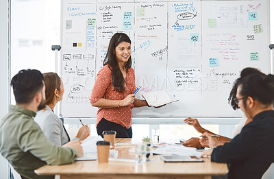 Buy stock photo Shot of a young businesswoman delivering a presentation to her colleagues in a modern office