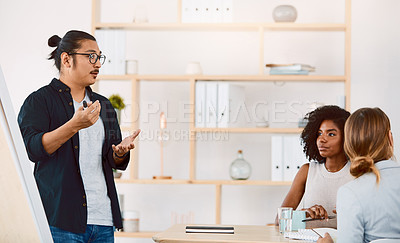 Buy stock photo Shot of a young businessman delivering a presentation to his colleagues in a modern office