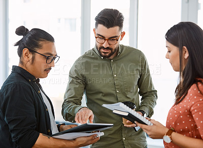 Buy stock photo Shot of young businesspeople using a digital tablet during a meeting in a modern office