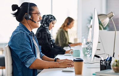 Buy stock photo Shot of a group of young call centre agents wearing headsets and working on their computers in an office