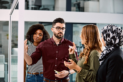 Buy stock photo Shot of a group of young businesspeople planning and writing notes on a glass wall in an office at work