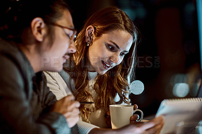 Buy stock photo Shot of a young businessman and businesswoman having a late night meeting at work