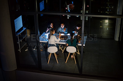 Buy stock photo Shot of a group of young businesspeople having takeout during a late night meeting at work