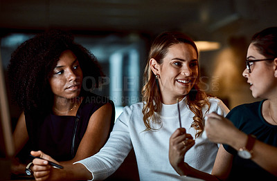Buy stock photo Shot of a group of young businesswomen having a discussion during a late night at work
