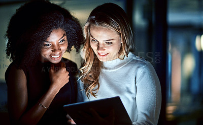 Buy stock photo Shot of two young businesswomen using a digital tablet during a late night at work