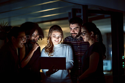 Buy stock photo Shot of a group of young businesspeople using a digital tablet during a late night at work