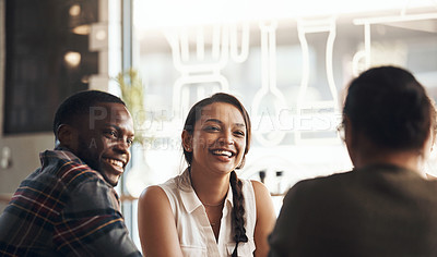 Buy stock photo Shot of a happy young diverse group sitting together in a coffee shop during the day