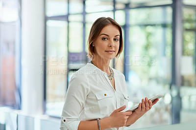 Buy stock photo Portrait of an attractive young businesswoman working on a digital tablet in her office