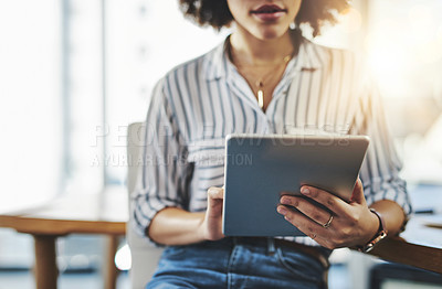 Buy stock photo Shot of an unrecognizable businesswoman using a digital tablet in her office at work