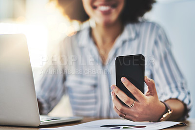 Buy stock photo Shot of an unrecognizable woman using her laptop and cellphone in her office at work