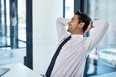 Buy stock photo Shot of a businessman looking relaxed while sitting at his desk