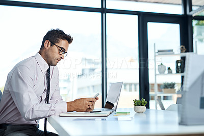 Buy stock photo Shot of a businessman using his cellphone while sitting at his desk