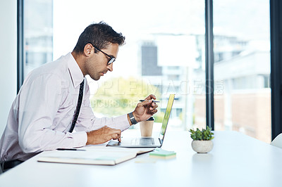 Buy stock photo Shot of a businessman working on his laptop