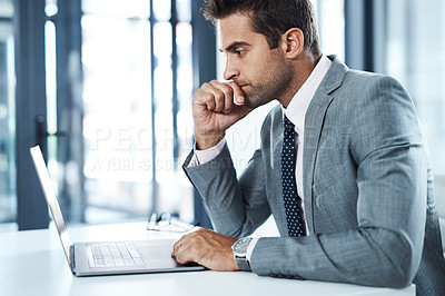 Buy stock photo Shot of a professional businessman sitting at his desk