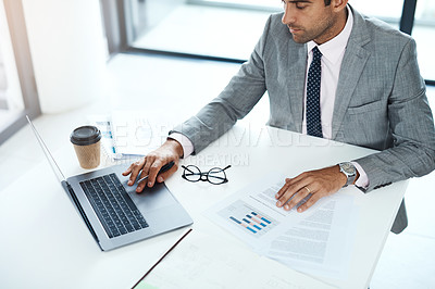 Buy stock photo Cropped shot of a businessman working with paperwork and his laptop