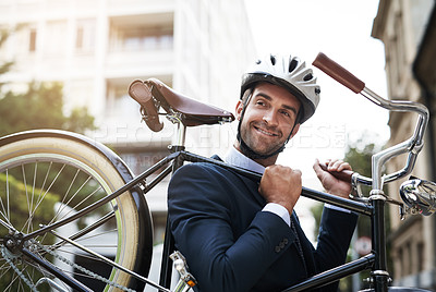 Buy stock photo Shot of a handsome young businessman carrying his bicycle while making his way to work in the morning