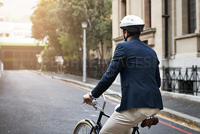 Buy stock photo Rearview shot of a handsome young businessman riding his bicycle to work in the morning