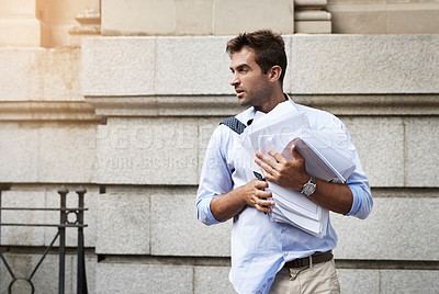Buy stock photo Shot of a stressed out young man holding a heap of paper documents while walking to work in the morning
