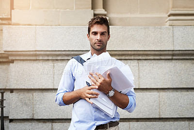 Buy stock photo Portrait of a stressed out young man holding a heap of paper documents while walking to work in the morning
