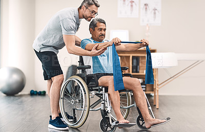 Buy stock photo Full length shot of a senior man in a wheelchair exercising with a resistance band along side his physiotherapist