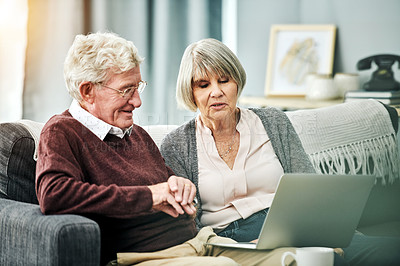 Buy stock photo Shot of an affectionate senior couple using a laptop while relaxing on their living room sofa at home