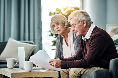 Buy stock photo Shot of a senior couple going over their finances while sitting on their living room sofa at home