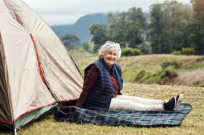 Buy stock photo Full length portrait of a senior woman sitting outside of a tent on her chosen camping spot
