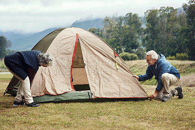 Buy stock photo Full length shot of an affectionate senior couple setting up a tent on their chosen camping spot