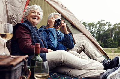Buy stock photo Full length shot of an affectionate senior couple taking photographs and enjoying wine while relaxing at their chosen camping spot