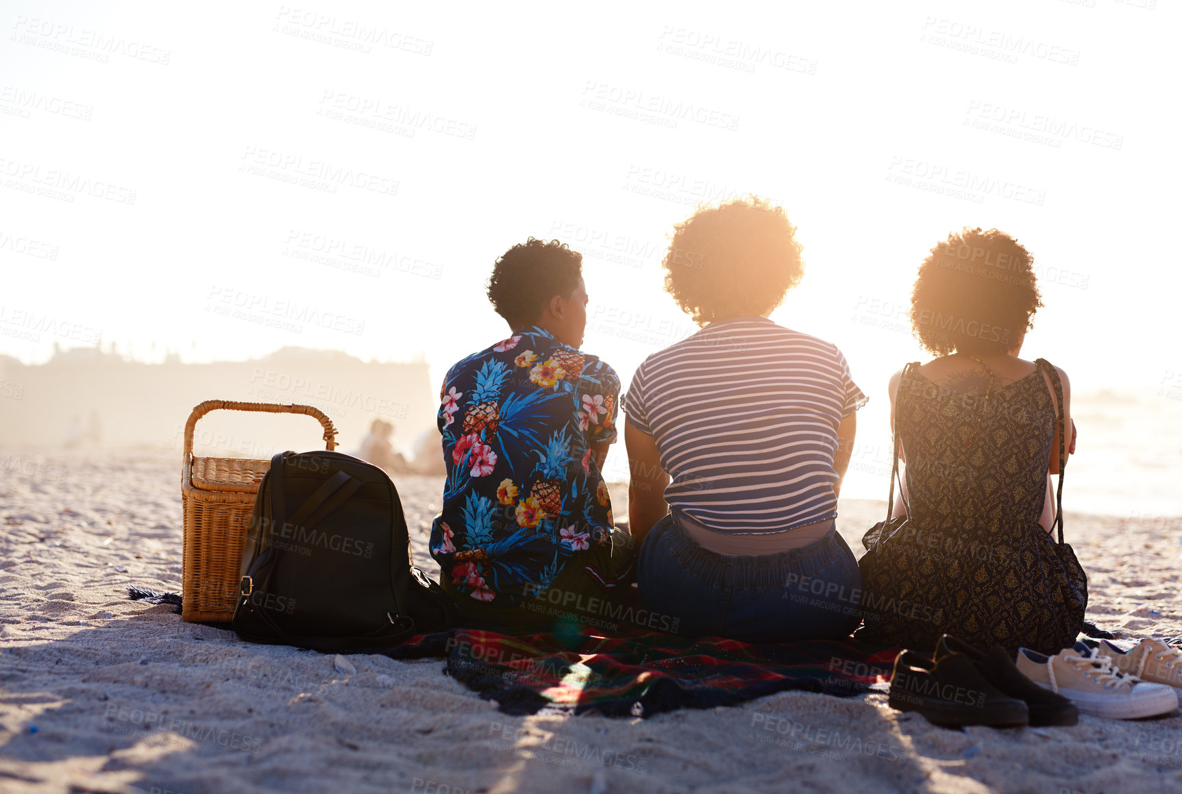 Buy stock photo Rearview shot of an unrecognizable diverse trio of women having a picnic on the beach during the day