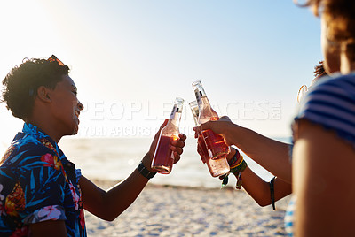 Buy stock photo Shot of an attractive young trio of women celebrating and having a drink together on the beach during the day