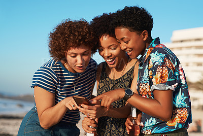 Buy stock photo Shot of three attractive young women huddled together and looking at a cellphone on the beach during the day